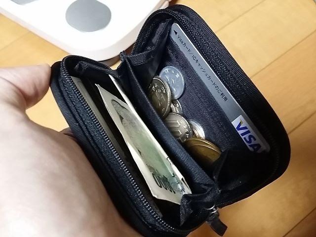 モンベルのミニジップワレットにお札や硬貨、カードが入っています。