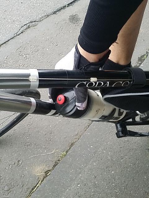 自転車のダウンチューブにあるドリンクボトルを掴んでいる