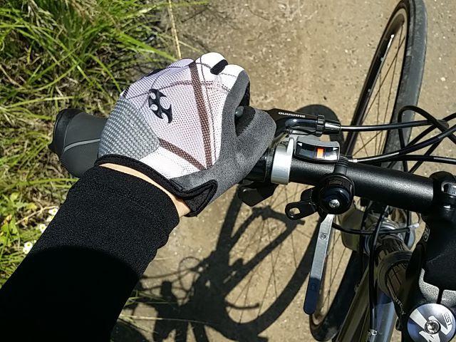 クロスバイクのフラットバーに装着したTOGSを手で握っている