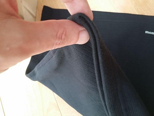 モンベルEXPウェストウォーマーを指で摘んで厚みを確認しています。