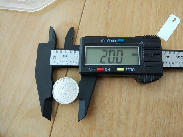 カーボン製デジタルノギスで一円玉を測定している