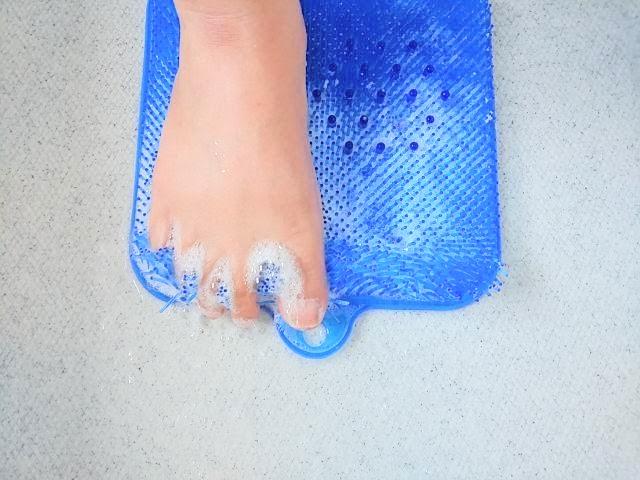 足洗いマットで指股を洗っている