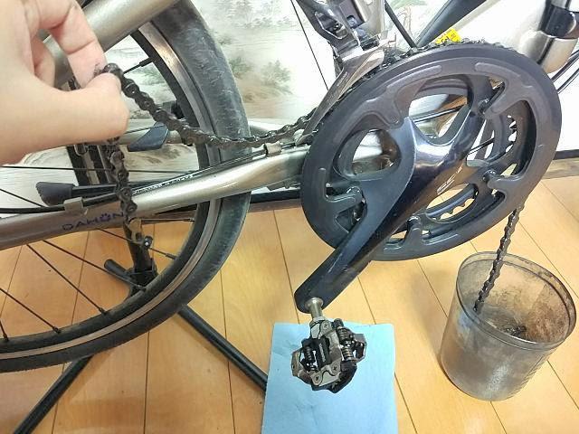 自転車チェーンを指で摘んでいる