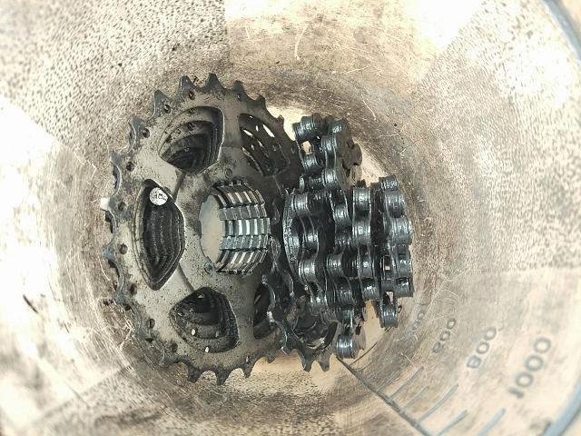 汚れた自転車チェーンとスプロケットが洗浄容器に入っている