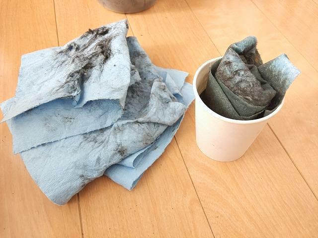 汚れたウェスと廃液の入った紙コップ