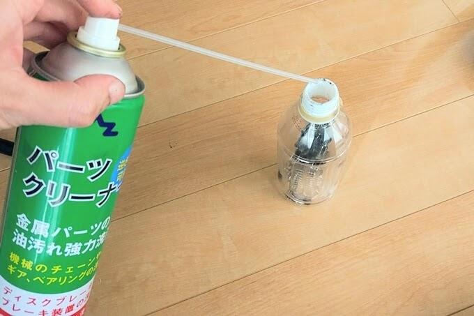 自転車チェーンが入っているペットボトルにパーツクリーナーを吹きかける