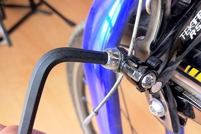 キャリパーブレーキのワイヤーを止めているネジを六角レンチで外す