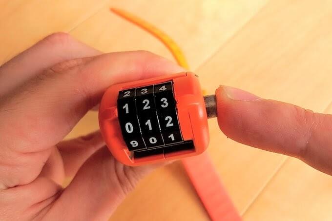 OTTOLOCKのダイヤル横にあるボタンを指で押している