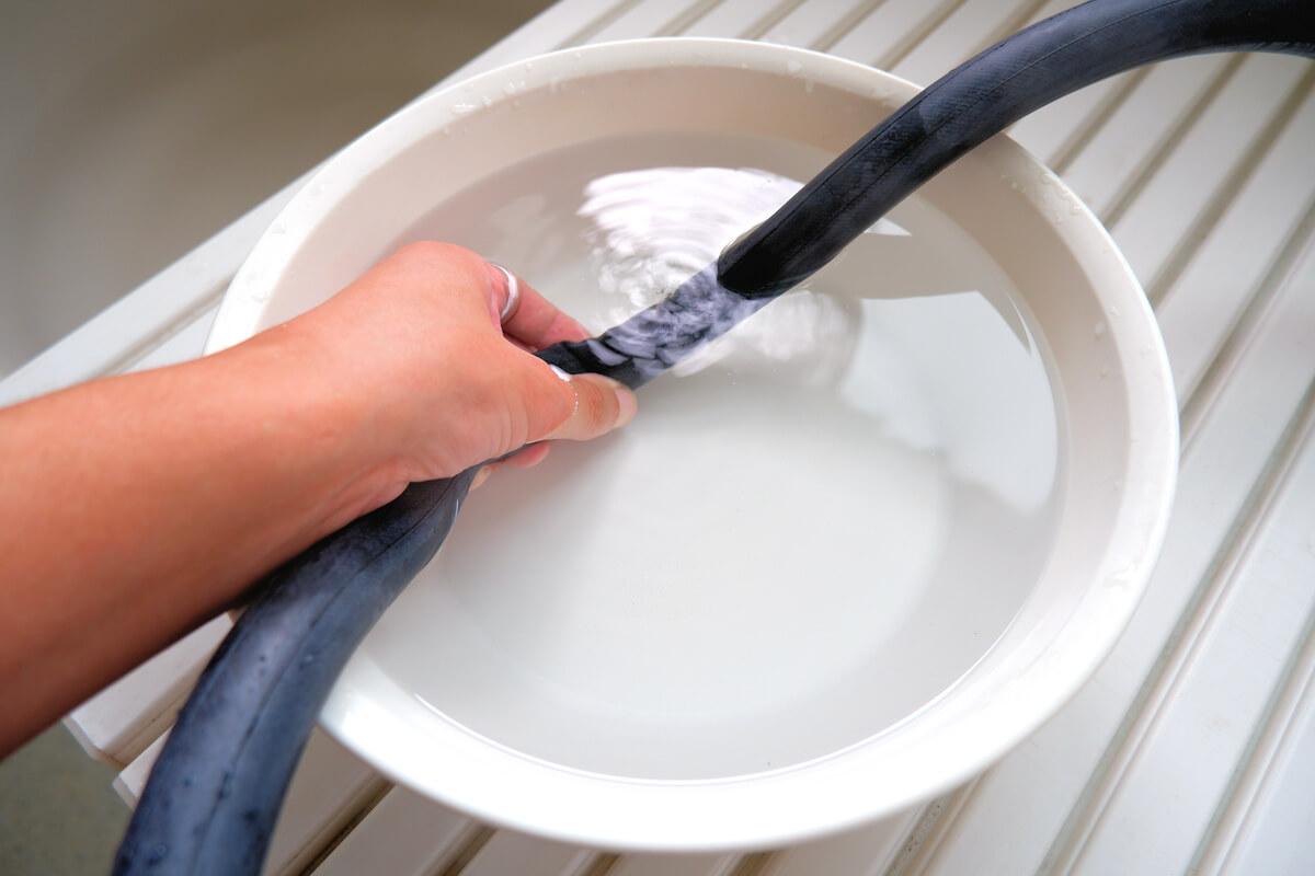 自転車チューブを水を張った洗面器につける