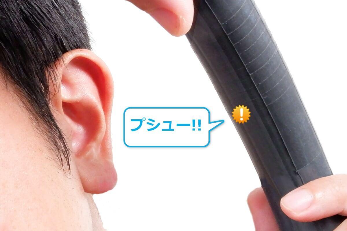 自転車チューブを耳に当ててパンク箇所を特定する
