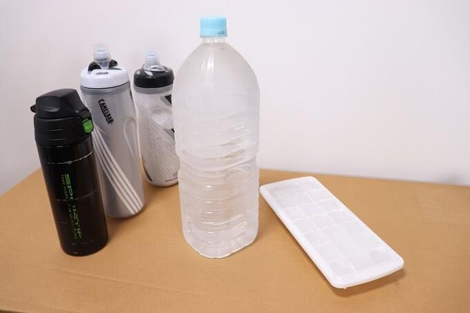 自転車ボトルに水と氷を入れている