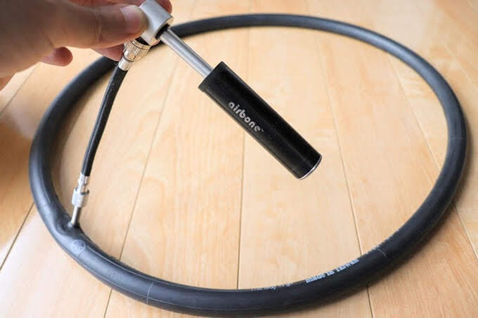 エアボーン スーパーミニポンプで自転車チューブに空気を入れている