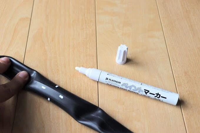 自転車チューブのパンク箇所を油性の白いペンでマーキングする