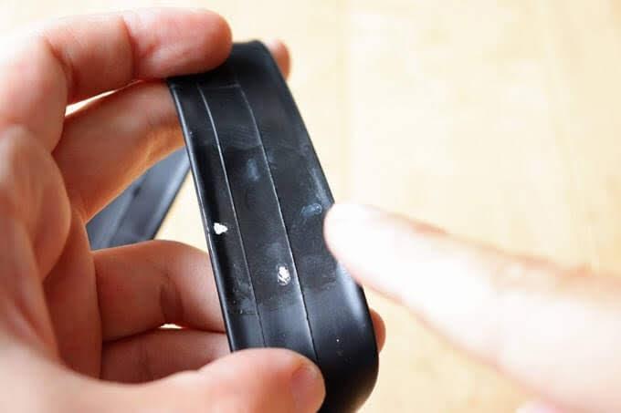 自転車チューブのパンク箇所にゴムのりをつけて指で塗っている
