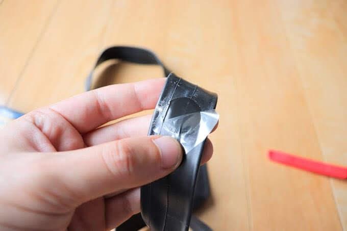 自転車用パンク修理パッチのフィルムを剥がしている