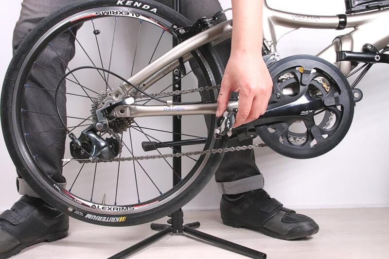 片手で自転車のクランクを回している