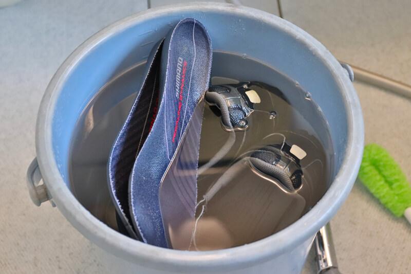 オスバンSを入れたバケツの水にサイクルシューズを入れる