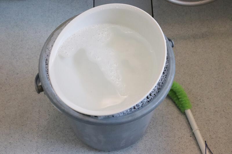 バケツに入れたシューズが浮かないように洗面器でフタをする