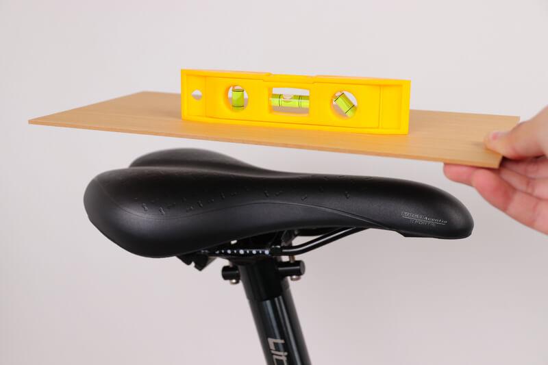 サドルの上に平らな板と水準器を乗せる