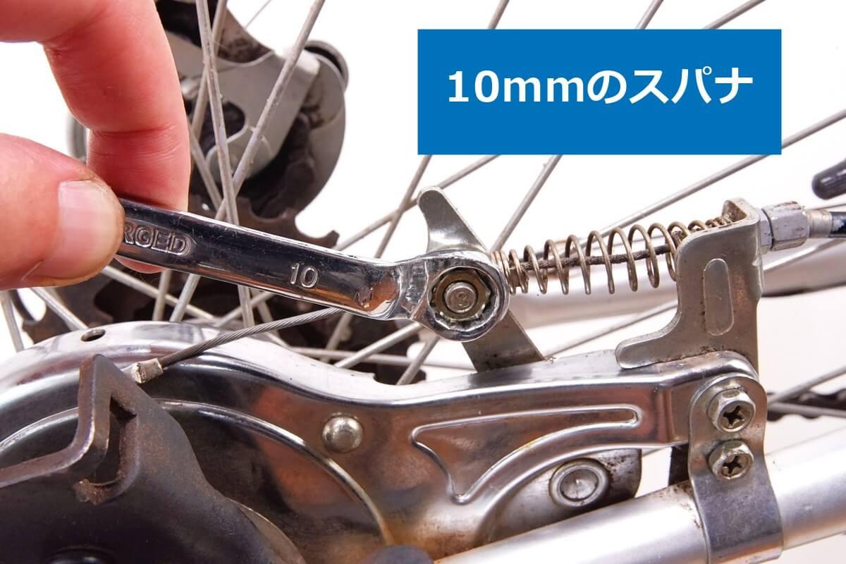 10mmのスパナでバンドブレーキのワイヤーを外す