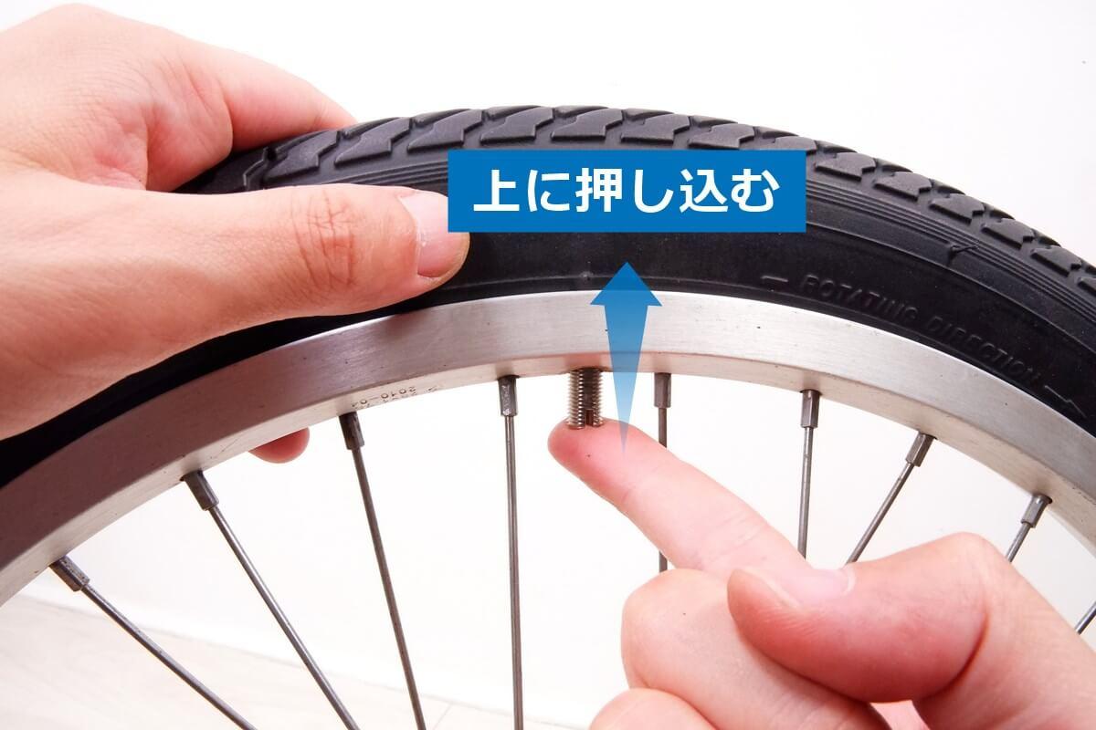 自転車チューブのバルブを上に押し込む