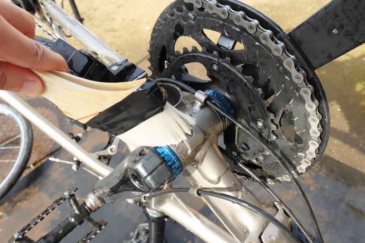 ハケを使って自転車の下側を洗う