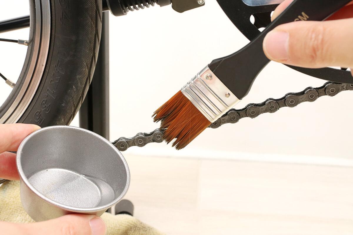 刷毛でグゥーキンアルファを自転車チェーンに塗る