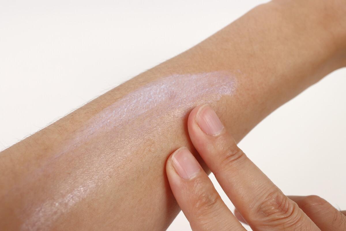 キャットアイの日焼け止めを腕に塗る